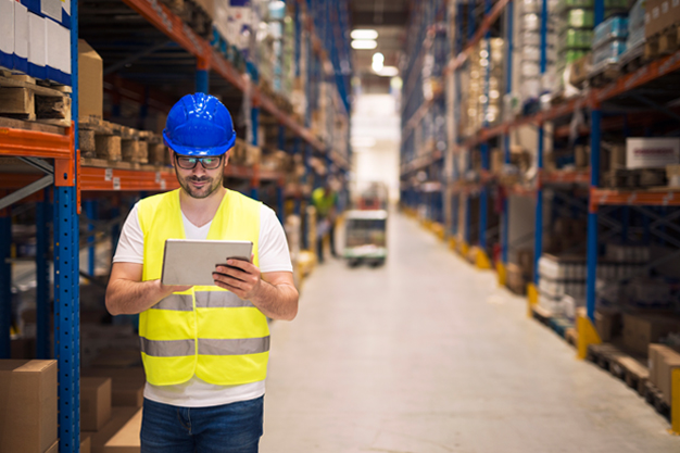 Warehouse worker checking inventory on his tablet while walking in large storage department with shelves and packages in the background.