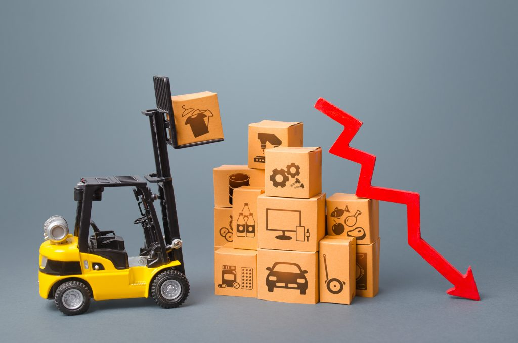 Forklift with boxes and red arrow down. Drop of performance production of goods. Import export trading, economic recession. Low demand and overstock. Overproduction. Slowdown in economic development.