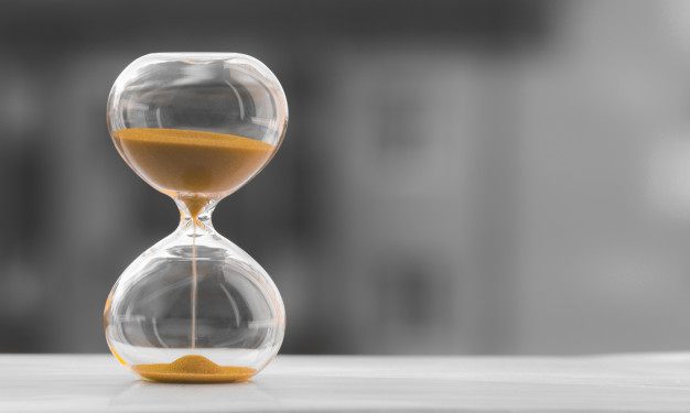 """""""Hourglass on a black white blurred background. time is money. Premium Photo"""""""