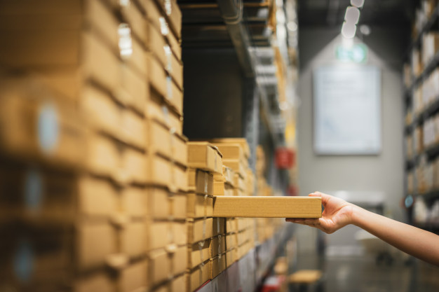 """""""Cardboard box package with blur hand of shopper woman picking product from shelf in warehouse. Premium Photo"""""""